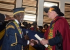 Chancelor Kofi Annan presents Professor Christopher Udry an honorary degree from the University of Ghana on March 23 Photo: Univesity of Ghana