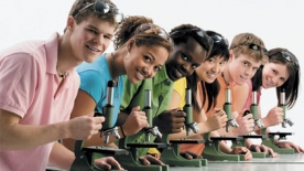 Students looking into microscopes - Photograph by Design Pics/Alamy