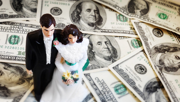 wedding cake groom and bride figurines on a pile of $100 bills - © stock.adobe.com