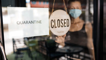 Small Business shop with Closed and Quarantine signs hanging in the window