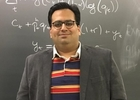 Portrait of Ahyan Panjwani in front of an equation on a chalkboard