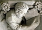 stone relief of male student reading a book