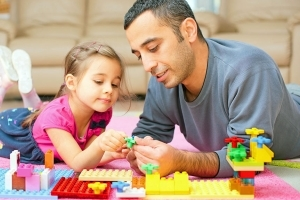 daughter and father playing with lego blocks